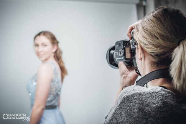 A photographer taking a side profile shot of a female model